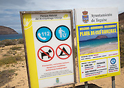 Signs at sandy beach Playa de las Conchas, Graciosa island, Lanzarote, Canary Islands, Spain