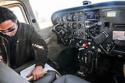 Pilot perform a preflight check on a cessna skyhawk inside the cockpit