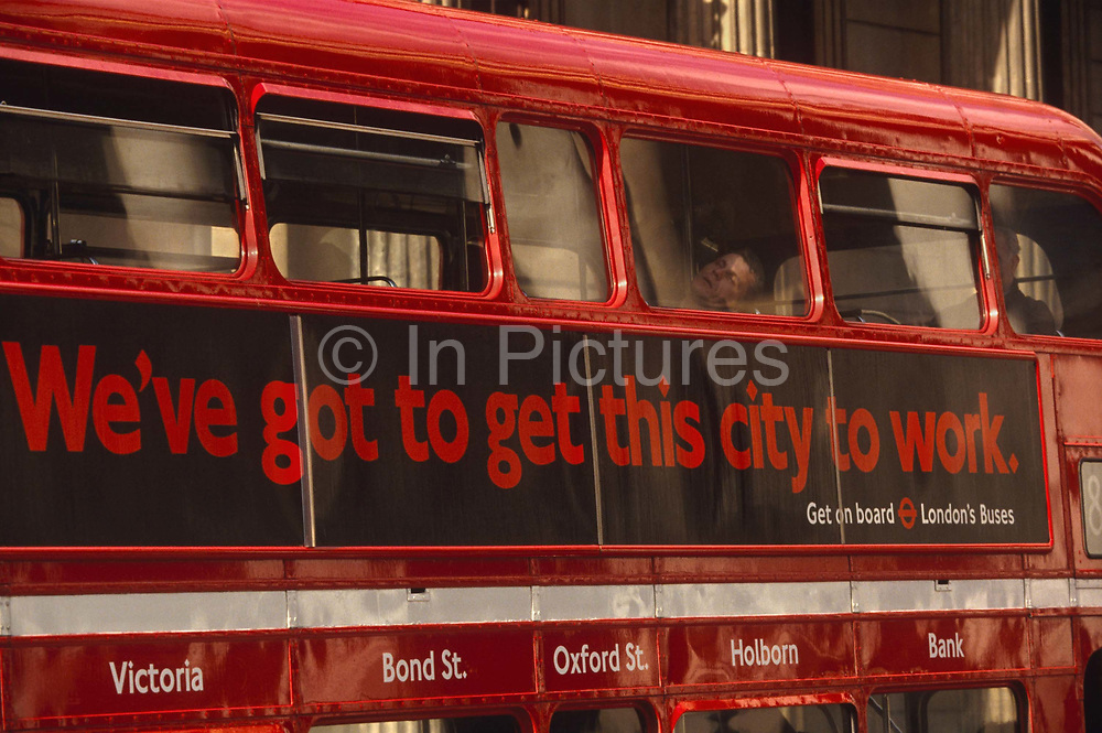 """A male passenger is asleep with his mouth open, leaning his head on a bus window as it passes the background pillars of the Bank of England in the financial district City of London. On the exterior of the bus are the words: """"We've got to get this city to work,"""" an advertising slogan used by London Transport to seduce commuters from their cars and back on to public transport which is one of the most expensive world capitals on which to travel by bus, train or underground. This style of bus is a traditional design called a 'Routemaster' which has been in service on the capital's roads since 1954 and is nowadays only seen on heritage routes such as these destination: Victoria, Bond Street, Oxford Street, Holborn and Bank (the Bank of England). From any angle, the bus is easily recognisable as that classic British transport icon.  The City of London has a resident population of under 10,000 but a daily working population of 311,000. The City of London is a geographically-small City within Greater London, England. The City as it is known, is the historic core of London from which, along with Westminster, the modern conurbation grew. The City's boundaries have remained constant since the Middle Ages but  it is now only a tiny part of Greater London. The City of London is a major financial centre, often referred to as just the City or as the Square Mile, as it is approximately one square mile (2.6 km) in area. London Bridge's history stretches back to the first crossing over Roman Londinium, close to this site and subsequent wooden and stone bridges have helped modern London become a financial success."""