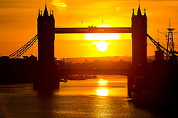 © Licensed to London News Pictures. 25/10/2015. London, UK. Sunrise behind Tower Bridge on the River Thames in London this morning. The skies are clear and the weather is much colder than yesterday in London for the first autumn morning after the clocks went back and UK time returns to Greenwich Mean Time (GMT) and officially marks the end of British Summer Time (BST).Photo credit : Vickie Flores/LNP
