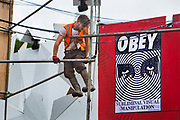 Erecting the Shangri La field, Glastonbury Festival 2016. In the background is a Shepard Fairey Obey poster. Glastonbury Festival 2016, United Kingdom. Glastonbury Festival is the largest greenfield festival in the world, and is now attended by around 175,000 people. Its a five-day music festival that takes place near Pilton, Somerset. In addition to contemporary music, the festival hosts dance, comedy, theatre, circus, cabaret, and other arts. Held at Worthy Farm in Pilton, leading pop and rock artists have headlined, alongside thousands of others appearing on smaller stages and performance areas.