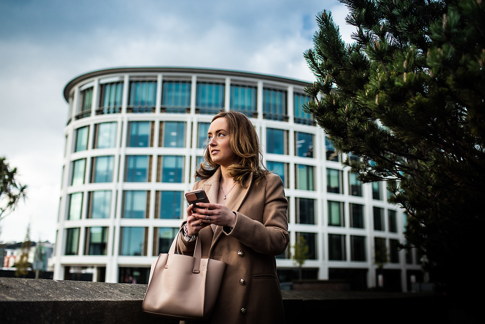 Elegant business woman using her smart phone in front of the International FInance Centre building in St Helier, Jersey, CI