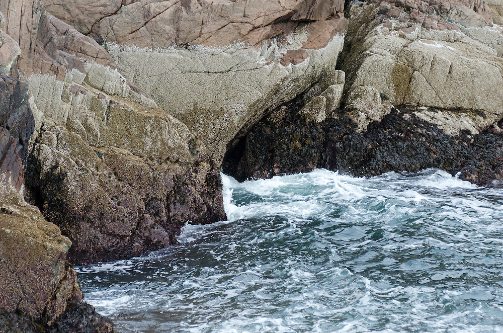 Winter waves crashing into a small sea cave near Seal Harbor, Maine.