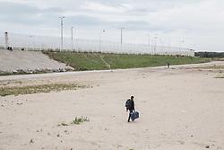 """Calais, Pas-de-Calais, France - 16.10.2016    <br />     <br />  Several high fences block the way towards the port and Euro Tunnel. """"Jungle"""" refugee camp on the outskirts of the French city of Calais. Many thousands of migrants and refugees are waiting in some cases for years in the port city in the hope of being able to cross the English Channel to Britain. French authorities announced that they will shortly evict the camp where currently up to up to 10,000 people live.<br /> <br /> Unter anderem mehrere hohe Zaeune versperren die Wege Richtung Hafen und Eurotunnel. """"Jungle"""" Fluechtlingscamp am Rande der franzoesischen Stadt Calais. Viele tausend Migranten und Fluechtlinge harren teilweise seit Jahren in der Hafenstadt aus in der Hoffnung den Aermelkanal nach Großbritannien ueberqueren zu koennen. Die franzoesischen Behoerden kuendigten an, dass sie das Camp, indem derzeit bis zu bis zu 10.000 Menschen leben Kürze raeumen werden. <br /> <br /> Photo: Bjoern Kietzmann"""