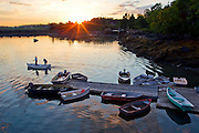 Lobstermen head to their lobster boat as the sun rises in Addison, Maine.
