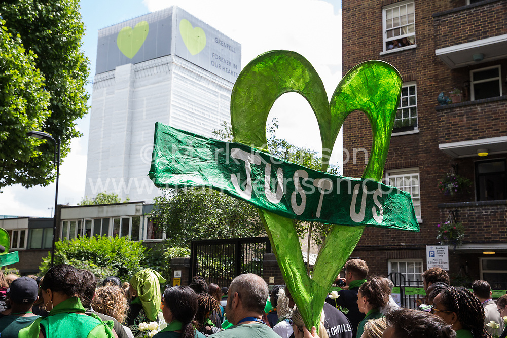 London, UK. 14th June, 2018. Members of the local community, faith leaders, politicians and wellwishers pass the Grenfell Tower, now covered, as they take part in a silent procession from St Helen's Church to the Wall of Truth to mark the first anniversary of the Grenfell Tower Fire.