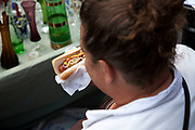 Large woman eats a hot dog on Portobello Road market, Notting Hill, West London. This famous Sunday market is when the antique stalls come out as well as the food stalls.