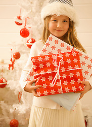 Close up of a girl standing by a Christmas tree holding gifts