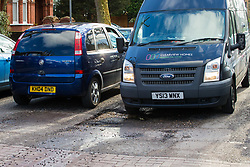 A van passes through a deep pothole on Brondesbury Road in London's expensive Queens Park, as the recent cold, wet weather has given rise to the increase in potholes and road surface deterioration in London. London, March 28 2018.