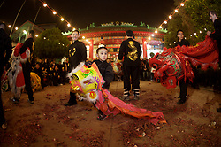 Stock photo of a young boy playing with a dragon costume head at the Chinese New Year celebrations in Houston Texas