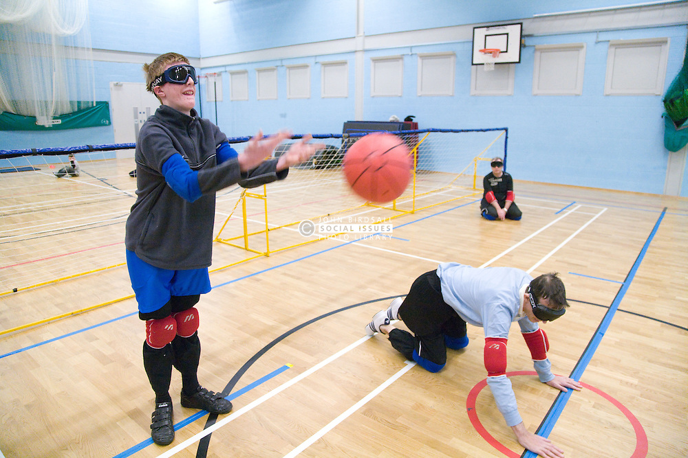 Winger Team Player standing up and throwing the ball during a Goalball game; a threeaside game developed for the visually impaired and played on a volleyball court, A specially adapted ball containing an internal bell is used,
