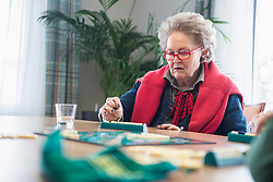 Senior woman playing board game in rest home