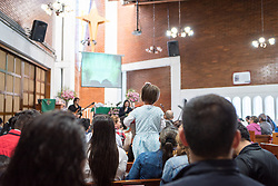 18 November 2018, Bogotá, Colombia: A young girl stands in the pews to see better during Sunday service in the Church of San Lucas. The church of San Lucas ('Saint Lucas') of the Evangelical Lutheran Church of Colombia, brings together a congregation of some 100 people in the southern areas of Bogotá. Located in the Kennedy area, the church has recently celebrated 50 years. As part of its ministry, the church runs a school and college, The Colegio Evangelico Luterano de Colombia (CELCO) San Lucas, offering education to just over 1,000 students aged 3-18. The school started as a social initiative offering care for children aged 0-4 in Bogotá's less wealthy neighbourhood, allowing the parents opportunities to go to work. 36 years after its foundation, the school employs 56 staff, of which 36 are teachers.