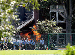 August 2, 2017 - Minneapolis, Minnesota, U.S.- Emergency personnel move away as a gas fire continues to burn following an explosion at Minnehaha Academy on Wednesday. One person was killed and one is unaccounted for in an explosion at the Minnehaha Academy upper school, officials said. Nine were injured, and three of them are in critical condition.  (Credit Image: © David Joles/TNS via ZUMA Wire)