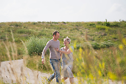 Mature couple running on field in summer, smiling