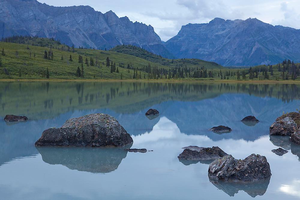 Reflections of distant mountains and lichen-covered boulders at dusk off the shore of a lake in Donoho Basin, Wrangell-St. Elias National Park, Alaska.