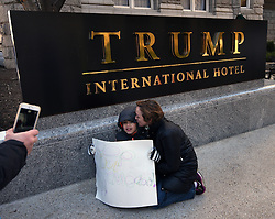 """December 10, 2016 - Washington, DC, USA - SHAWNA BADER-BLAU from DC kisses her son JAMES BLAU, 8 years old, in front of Trump hotel sign.  Children's Rally for Kindness takes place at Trump International Hotel in Washington DC on December 10, 2016 organized by the Takoma Parents Action Coalition.  According to their FaceBook page, it was a call to President-elect Donald Trump: ''to remember these lessons as he prepares to take office and implement policies that will affect the lives of children and families across our diverse nation.''.''All over the world, across cultures and countries, children learn the same basic lessons: .Ã'be kind,Ã"""" .Ã'tell the truth,Ã"""" .Ã'be fair,Ã"""" .Ã'respect everyone,Ã"""" .Ã'treat others the way you want to be treated,Ã"""" .Ã'donÃ•t touch others if they donÃ•t want to be touched. (Credit Image: © Carol Guzy via ZUMA Wire)"""