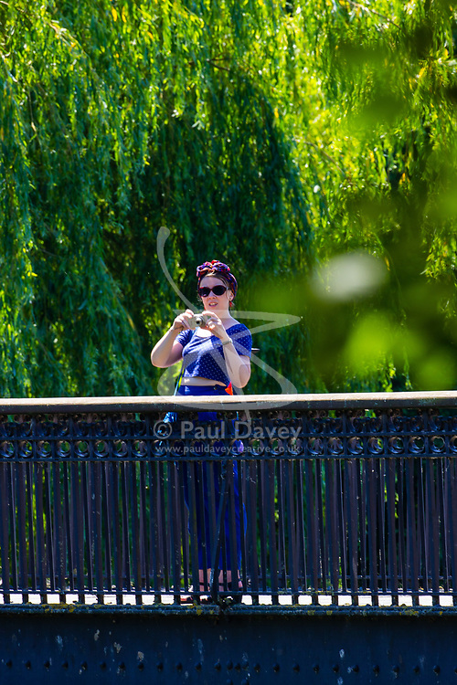 A woman takes pictures from a bridge over the boating lake in Regents Park, London, as the heatwave continues to grip the capital. London, June 29 2018.