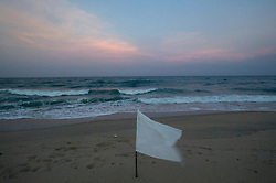 A lone white flag is seen on the shore of Dutch Bar in memory of those lost in the tsunami, Batticaloa, Sri Lanka, Feb. 5, 2005. Residents of the small Christian village spent more than six weeks in a makeshift refugee camp at the local convent recovering from the devastating tsunami that hit the eastern and southern borders of Sri Lanka. They were then moved into another temporary living camp, while awaiting the building of new homes. More than 150 members in this community of less than 1000 people died in the tragic event.