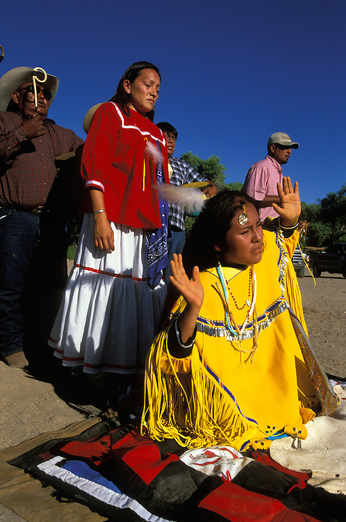An Apache girl dressed in buckskin clothes dances in a kneeling positon at her Sunrise Dance, a first menstruation rite, the San Carlos Indian Reservation, Arizona, USA. During the ceremony the girl 'becomes' Changing Woman, the mythical founder of the Apache Tribe, and this part of the ceremony is an enactment of when Changing Woman was impregnated by the sun and gave birth to a son.  Behind the girl stands her godmother and behind her the medicine man and his assistants sing and beat their drums.