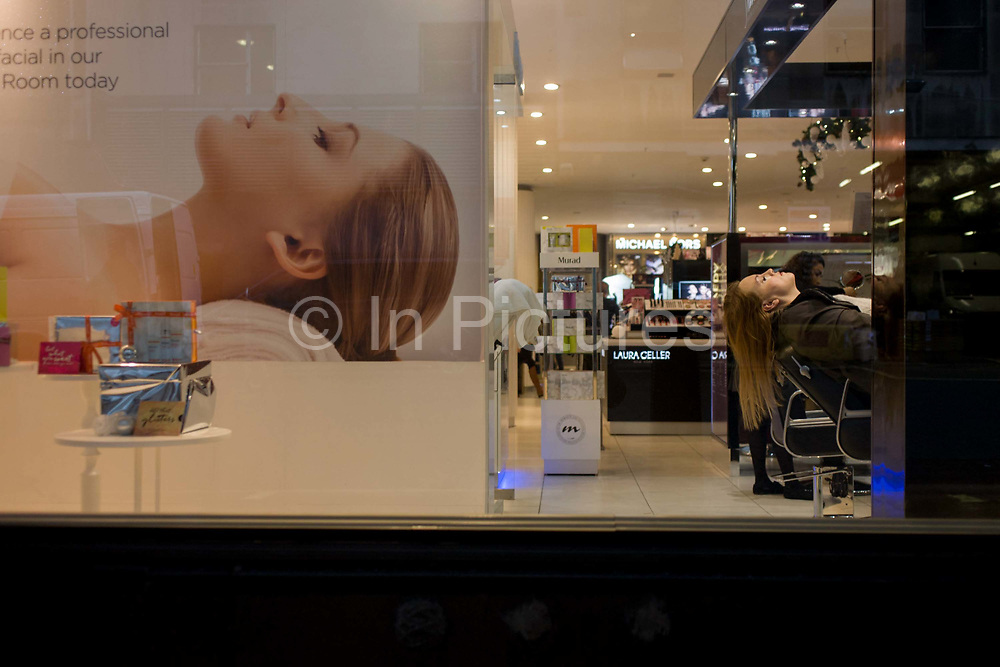Large image of a model and real-life lady customer also reclined for beauty treatment, in the window of Debenhams on London's Oxford Street. The woman to the right is lying prone, in a horizontal position, awaiting further treatment by a shop assistant in the beauty department of this central London retailer, a department store on Oxford Street a short time before Christmas. We look in from the outside to see the female heads backed towards each other in a matching posture.