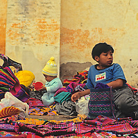 Central America, Guatemala, Antigua. A young boy attends his baby sibling as well as a selection of Guatemalan textiles in Antigua, Guatemala.