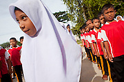 """Sept. 27, 2009 -- PATTANI, THAILAND: School children in formation before class at the Gahong School in Pattani, Thailand, Sept 27. Most of the children in the school are Muslim. Schools and school teachers have been frequent targets of Muslim insurgents in southern Thailand and the army now provides security at many government schools.  Thailand's three southern most provinces; Yala, Pattani and Narathiwat are often called """"restive"""" and a decades long Muslim insurgency has gained traction recently. Nearly 4,000 people have been killed since 2004. The three southern provinces are under emergency control and there are more than 60,000 Thai military, police and paramilitary militia forces trying to keep the peace battling insurgents who favor car bombs and assassination.  Photo by Jack Kurtz / ZUMA Press"""
