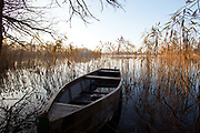 A solitary boat in Uckermarkische Seen Natural park, part of the The Feldberg Lake District Nature Park containing large lakes, kettle bogs, and an abundance of plant and animcal species. Brandenburg, Germany.