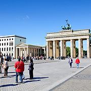 Groups of tourists walking in Pariser Platz in front of the Brandenburg Gate (Brandenburger Tor) in Berlin on a day with a beautiful clear blue sky in the background.