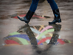United States, Washington, Mt. Vernon, woman in rubber boots walking by puddle with reflection of banners