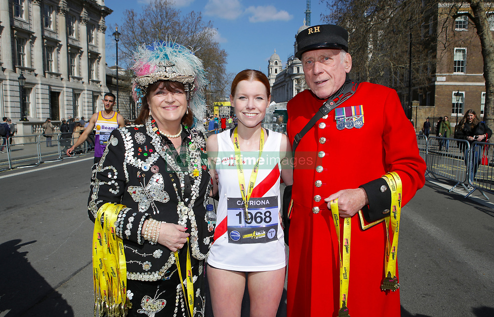 A competitor poses with a chelsea pensioner and a pearly queen during the 2019 London Landmarks Half Marathon.