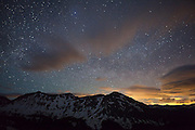 The MIlky Way sparkles in the night sky over the Never Summer Mountains of Colorado (Baker Mountain and Mount Stratus) while the distant lights of Denver and the Front Range paint the clouds orange.