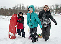 """Giovanni, Sincere and their """"Ya Ya"""" head up the sliding hill at Memorial Park during Tuesday's """"snow day"""".  (Karen Bobotas Photo/for The Laconia Daily Sun)"""