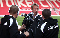 Swansea City manager Graham Potter (centre) speaks so the a Swansea tv channel before the game
