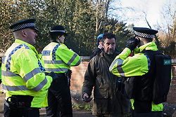 Denham, UK. 6 February, 2020. Police officers talk to environmental activists from Save the Colne Valley, Stop HS2 and Extinction Rebellion who were walking at a snail's pace along a road so as to block for several hours a security vehicle and truck delivering fencing and other supplies to be used for works associated with the HS2 high-speed rail link close to the river Colne at Denham Ford. Some activists also collected litter during the action.