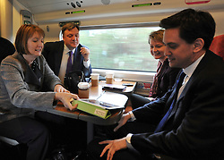 © Licensed to London News Pictures. 16/03/2012. London, UK. (left to right) Ed Balls, Yvette Cooper, Ed Miliband and Harriet Harmen look at Mrs Harmen's iPad tablet computer. Leader of the Labour Party, Ed Miliband and members of his Shadow Cabinet travel to Labour's Youth Conference in Coventry this morning, 16 March 2012, by train from London Euston Station. Photo credit : Stephen SImpson/LNP