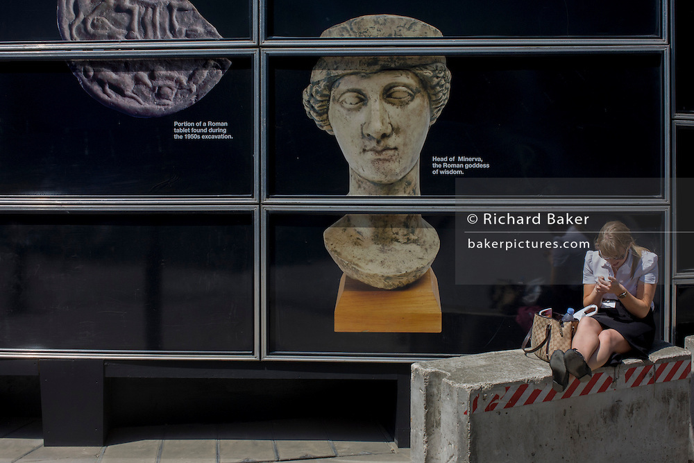 Walbrook Roman archeology Minerva Goddess figure and modern woman using her smartphone in the City of London. Walbrook Roman archeology Minerva Goddess figure and modern woman using her smartphone by a construction hoarding in the City of London.
