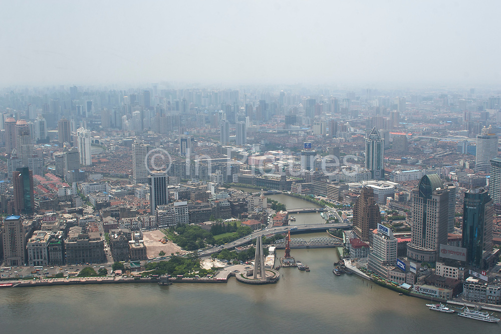 View looking from The Oriental Pearl Tower in Pudong, across the Huang Pu River to Puxi and Suzhou Creek in Shanghai's downtown area in Shanghai, China. The Bund's western buildings lines the bottom of the view as modern Shanghai's high-rise skyscraper filled landscape raises up behind.