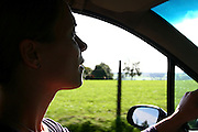 Belgium, Woman driving a car the Belgian rural landscape in the background