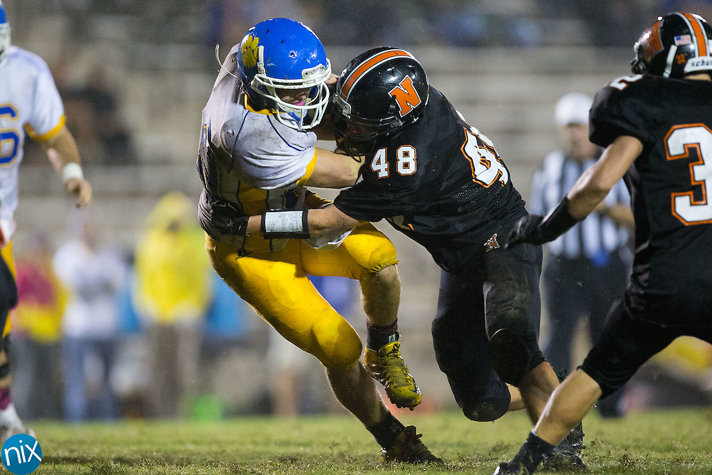 Mount Pleasant Tigers running back Cody Reece (20) is hit by Sam Newhouse (48) of the Northwest Cabarrus Trojans at Trojan Stadium October 1, 2015, in Concord, North Carolina.  The Tigers defeated the Trojans 42-0.  (Brian Westerholt/Special to the Tribune)