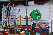 Construction workers on site behind barrier fencing beneath cartoon character in Wardour Street, London.