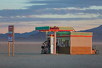 "Drinking from the gas pump at Awful's Gas & Snack<br /> by: Matthew Gerring & Crank Factory<br /> from: San Francisco, CA<br /> year: 2019<br /> <br /> Awful's Gas & Snack: Your Gateway to the Big Wild! See one of the few remaining gasoline stations, painstakingly preserved since the mid-21st century. Travel back to a time when hardy men roamed the ""open road"" seeking fortune & freedom. Wilderness passes & provisions available. NO GAS AVAILABLE FOR PURCHASE, PLEASE DON'T ASK.<br /> <br /> URL: http://awfulsgas.com<br /> Contact: awfuls@awfulsgas.com<br /> <br /> https://burningman.org/event/brc/2019-art-installations/?yyyy=&artType=H#a2I0V000001AVwVUAW"