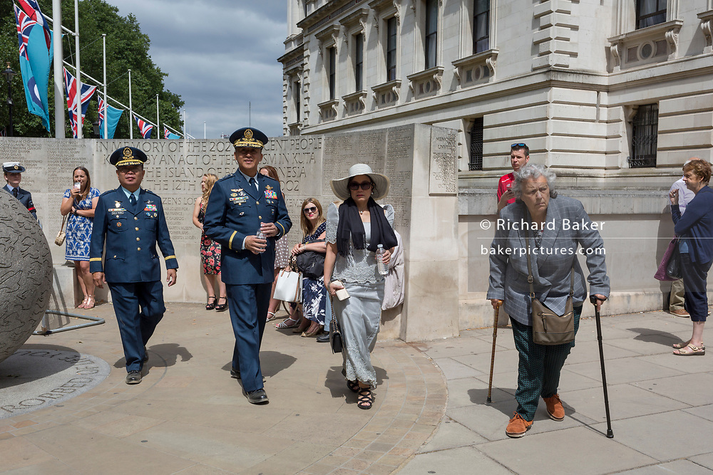 On the 100th anniversary of the Royal Air Force (RAF) and following a flypast of 100 aircraft formations representing Britain's air defence history which flew over central London, Colonel Augusto D Dela Pena (left) and Lt. Gen. Galileo Gerard Kintanar Jr. (right) of the Phillipines Air Force (PAF) leave Horseguards, passing the London memorial to those killed in the 2002 Bali bombing, on 10th July 2018, in London, England.