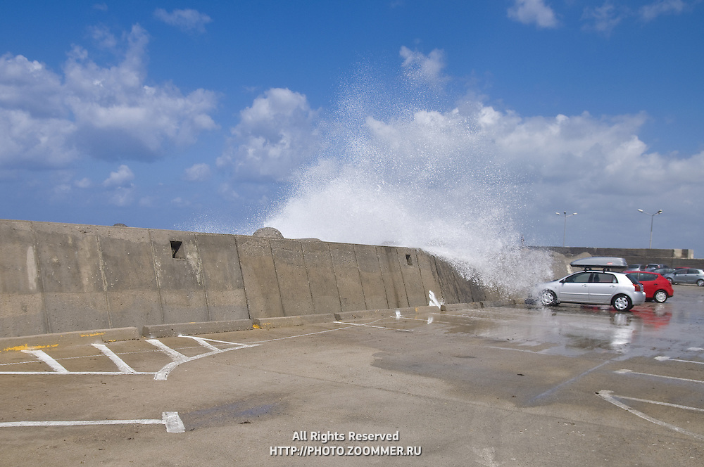 Sea waves crashing over car in parking lot in Rethymno, Crete