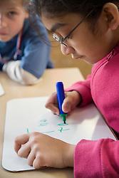 Girl sitting at desk in classroom practising writing skills,