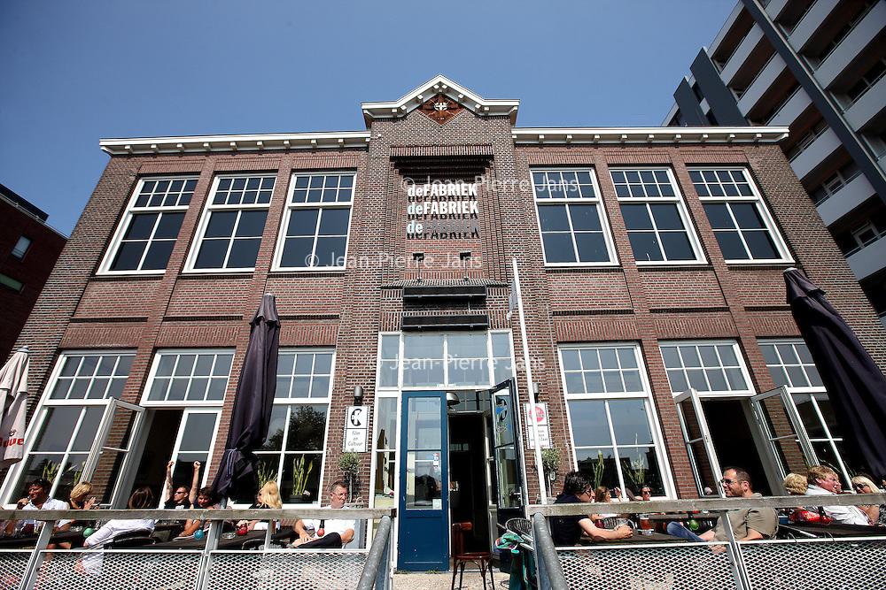 Nederland, Zaandam , 5 juli 2013.<br /> Wandeling door de binnenstad van Zaandam.<br /> Starten bij De Werf aan de Oostzijde. Daarvandaan kun je lopen op een soort boulevard tussen de flats en het water. De eerste stop is De Fabriek, filmhuis en eetcafé met terras aan de Zaan met uitzicht op de sluis. Daarna de sluis zelf.<br /> Dan langs het winkelgebied richting de Koekfabriek: Het oude Verkade pand dat is verbouwd en waar nu de bieb en sportschool en restaurant etc. in zitten.<br /> (Dat is aan de overkant van het startpunt) en misschien nog de Zwaardemaker meepakken aan de Oostzijde. Dat is een oud pakhuis die Rochdale enige jaren geleden heeft verbouwt tot appartementen met een stukje Nieuwbouw.<br /> Ook doen: het Russische buurtje vlakbij de Zaan. Dit jaar staat Rusland in de schijnwerpers en Zaandam heeft een speciale band met Rusland, vanwege het Czaar Peterhuisje en de Russische buurt. <br /> Op de foto: Café terras en filmhuis De Fabriek aan de Oostzijde<br /> Foto:Jean-Pierre Jans
