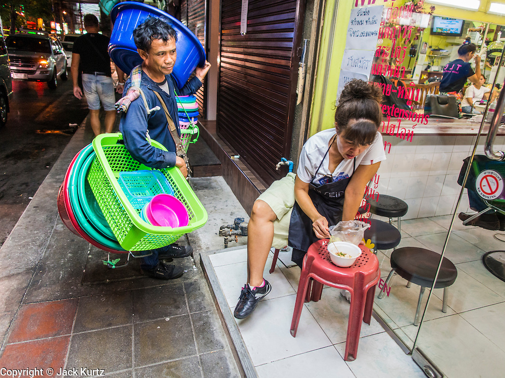 """22 MAY 2014 - BANGKOK, THAILAND: A street vendor sells plastic tubs and baskets near the Soi Cowboy """"adult entertainment"""" district after the Thai army announcement of a coup replacing the civilian government. The Thai army suspended civilian rule, suspended the constitution and declared the """"military takeover of the nation."""" The announcement came just before evening as a meeting between civilian politicians and the army was breaking up with no progress towards resolving the country's political impasse. Civilian politicians were arrested when the meeting ended. The army also declared a curfew from 10PM until 5AM.    PHOTO BY JACK KURTZ"""