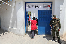 May 6, 2018 - Tunis, Tunisia - An armed Tunisian soldier stands guard outside a primary school turned into a polling station during the municipal election, as Tunisian woman pushing a baby stroller enters the polling station in Ariana governorate near the capital Tunis, on May 6, 2018..Seven years after their uprisings, Tunisians headed to the polls for the Tunisia's first free municipal election since long-time president Zine El-Abdine Ben Ali fled the country..The vote will mark a step towards decentralisation of the power in Tunisia, which was suffering of hyper-centralised rule. (Credit Image: © Chedly Ben Ibrahim/NurPhoto via ZUMA Press)