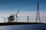 Solar panels, wind turbines and electricity pylons at the Solar array of community project Low carbon Gordano, a community renewable energy project. Delivering 1,750HWh per annum. Avon, Somerset.