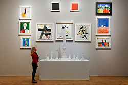 """© Licensed to London News Pictures. 07/02/2017. London, UK. A staff member looks at a collection of works by Kazimir Malevich, including his famous """"Black Square"""" and """"Red Square"""", at the preview of an exhibition entitled """"Revolution Russian Art 1917-1932"""", which marks the centenary of the Russian Revolution.  The exhibition runs from 11 February to 17 April 2017 at the Royal Academy of Arts in Piccadilly. Photo credit : Stephen Chung/LNP"""
